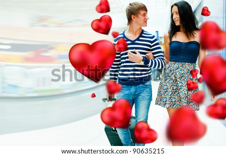 Portrait of young couple walking together at airport hall with their luggage. They are very happy to fly to warm country on holidays. Hearts around them. Valentine concept - stock photo