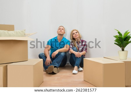Portrait Of Young Couple With Cardboard Boxes In New Home Looking Up - stock photo