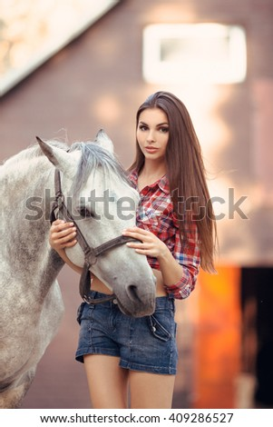 Portrait of young cowgirl and white horse outdoors near stable - stock photo