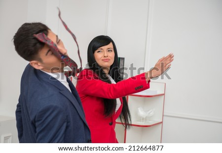 Portrait of young crying  business woman in red jacket  giving a slap in the face to her flirting colleague in office, relationship at work concept - stock photo