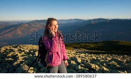 Portrait of young cute female backpacker standing on rocky top of the mountain, smiling, looking to the sun and talking cell phone. Side view. Healthy lifestyle concept. Sunny autumn evening. - stock photo