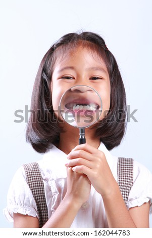 Portrait of young cute girl holding magnifying glass - stock photo