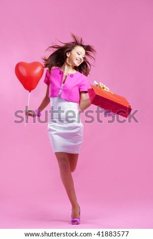 Portrait of young cute shopaholic girl running on pink studio background - stock photo