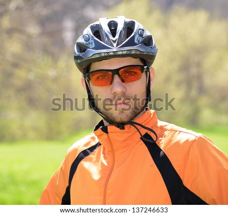 Portrait of Young Cyclist in Helmet and Glasses - stock photo