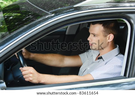 Portrait of young dark-haired handsome man driving car. - stock photo