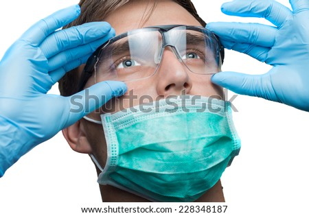 Portrait of young dentist doctor with blue eyes wearing surgical mask, blue gloves and safety glasses - stock photo