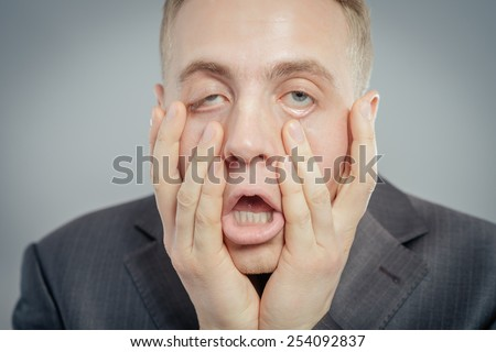 Portrait of young desperate businessman pulling his face down isolated on gray background - stock photo