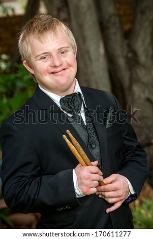 Portrait of young disabled boy with drumsticks outdoors. - stock photo