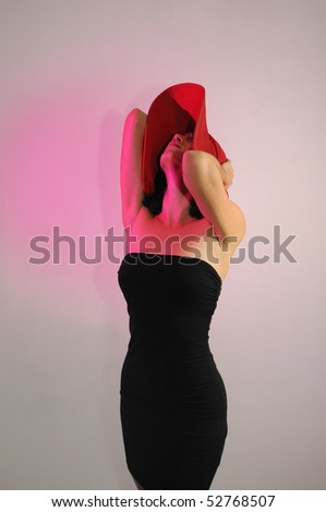 Portrait of young elegant woman wearing black dress and hat - stock photo