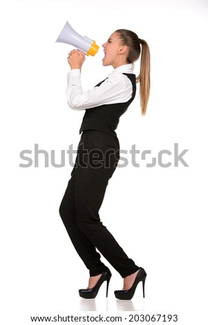 Portrait of young emotional beautiful woman yelling into a megaphone, on a gray background - stock photo