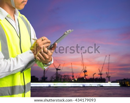 Portrait of young engineer taking notes - stock photo