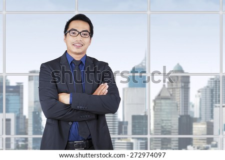 Portrait of young entrepreneur in business suit, smiling at the camera near the window at office - stock photo