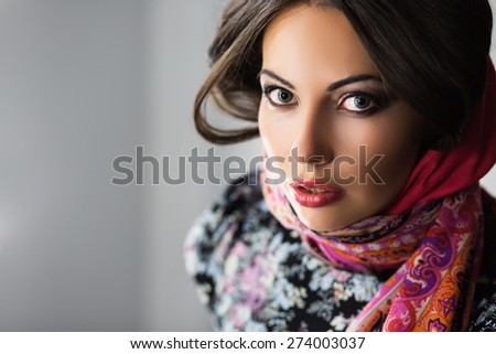 Portrait of young excited brunette in flowered dress and scarf - stock photo