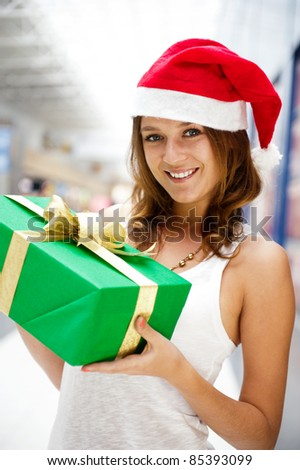 Portrait of young excited pretty woman wearing Santa Claus helper hat standing inside shopping mall smiling and holding christmas gift. - stock photo