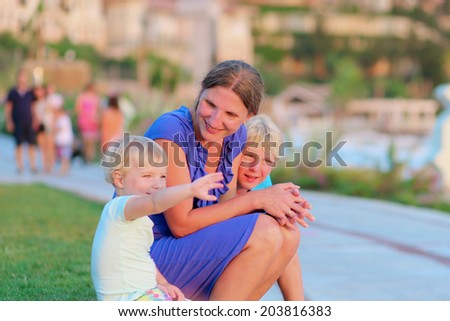 Portrait of young family, active woman with two children, enjoying summer vacation relaxing on the beach promenade looking at sunset in beautiful tropical resort. Selective focus on mother. - stock photo
