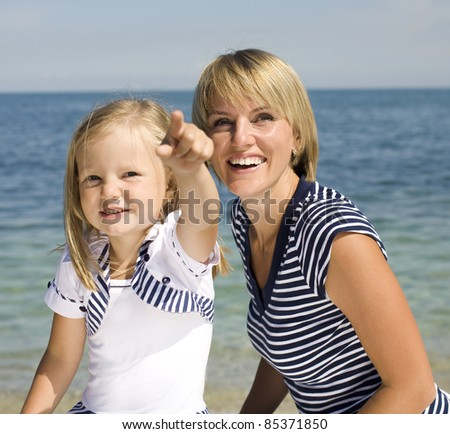 Portrait of young family having fun on the beach, mother and daughter at sea - stock photo