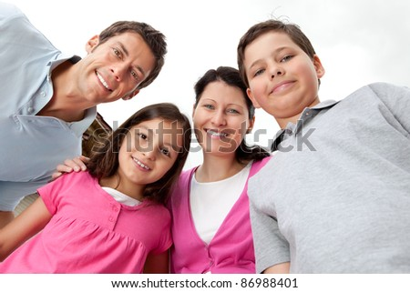 Portrait of young family looking happy against sky - stock photo