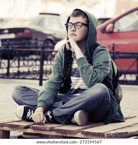Portrait of young fashion man sitting on a city sidewalk - stock photo