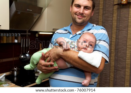 Portrait of young father is holding the baby on the kitchen - stock photo