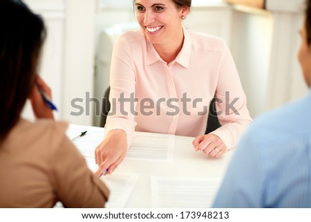 Portrait of young female bank manager working on agreement contract and explaining the application form to a young woman at office - stock photo