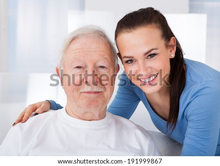 Portrait of young female caretaker with senior man at nursing home - stock photo