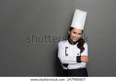 portrait of young female chef crossed arm against gray background - stock photo