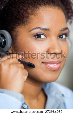 Portrait of young female customer service representative wearing headset in office - stock photo