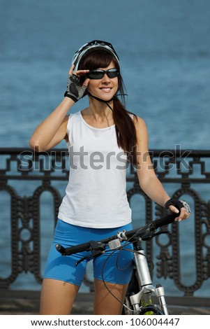 Portrait of young female cyclist standing with her bike on the city river wharf looking away - stock photo