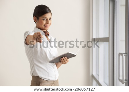 Portrait of young female executive giving pen to write in diary - stock photo