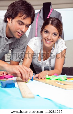 Portrait of young female fashion designer smiling while coworker draws line on fabric with chalk - stock photo