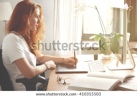 Portrait of young female freelancer working at home using digital tablet. Redhead woman designer in white T-shirt hand drawing on graphic tablet while sitting in front of computer screen. Flare sun  - stock photo
