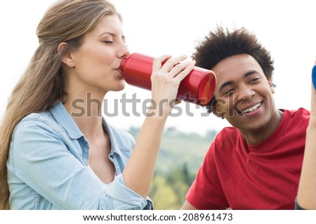 Portrait Of Young Female Hiker Drinking Water From Thermos Outdoor - stock photo