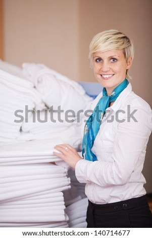 Portrait of young female housekeeper stacking sheets in stock room - stock photo