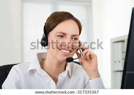 Portrait Of Young Female Operator With Headset In Call Center - stock photo