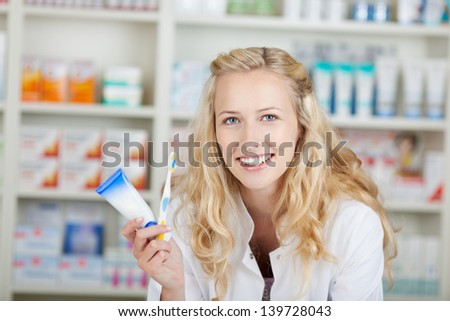 Portrait of young female pharmacist with toothpaste and toothbrush in pharmacy - stock photo