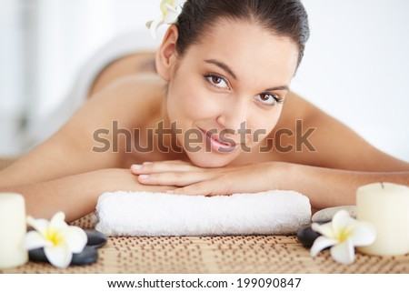 Portrait of young female ready for massage looking at camera - stock photo