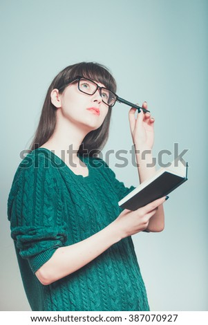 portrait of young female student thinking with pen and notepad with glasses isolated on a gray background - stock photo