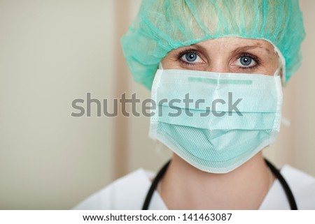 Portrait of young female surgeon wearing mask in hospital - stock photo