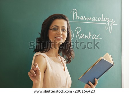 Portrait of young female teacher holding chalk and book against green board - stock photo