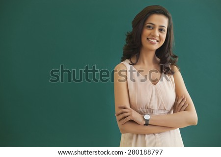 Portrait of young female teacher with arms crossed standing against green board - stock photo