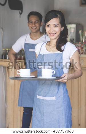 portrait of young female waitress serving coffe at the cafe - stock photo