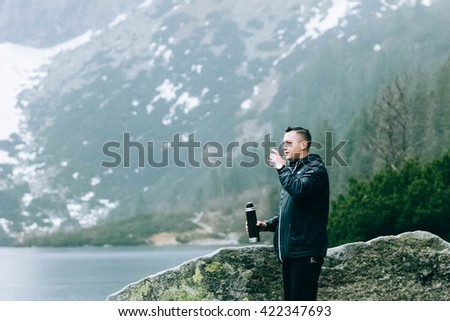 Portrait of young fit male hiker drinking tea on top of the mountain - stock photo