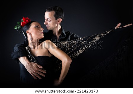 Portrait of young flamenco dancers in beautiful dress on black background. - stock photo