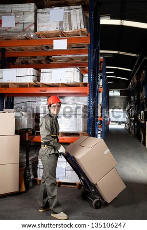 Portrait of young foreman pushing handtruck with cardboard boxes at warehouse - stock photo