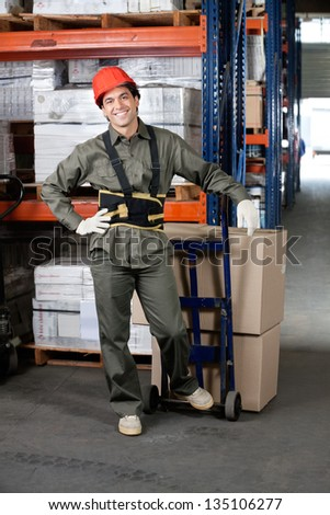 Portrait of young foreman with handtruck loading cardboard boxes at warehouse - stock photo