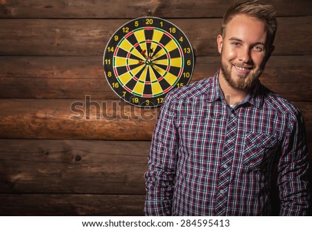 Portrait of young friendly lucky man against old wooden wall with darts game. Concept: Hit in purpose. Photo.  - stock photo