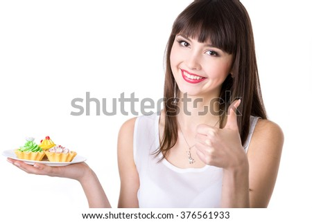 Portrait of young friendly smiling woman holding in her hand plate with delicious cream tart cakes, looking at camera with cheerful expression, showing thumbs up, studio, white background, copy space - stock photo