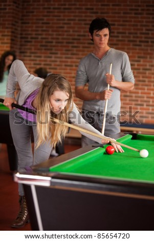 Portrait of young friends playing snooker in a student home - stock photo