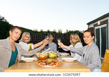 Portrait of young friends toasting drinks at table during outdoor party - stock photo