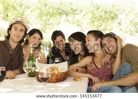 Portrait of young friends with drinks and bread basket at table enjoying party - stock photo
